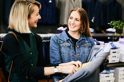 Two women smiling and looking at a jacket.