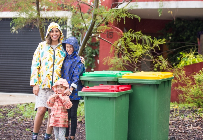 Family standing next to the new FOGO bins.