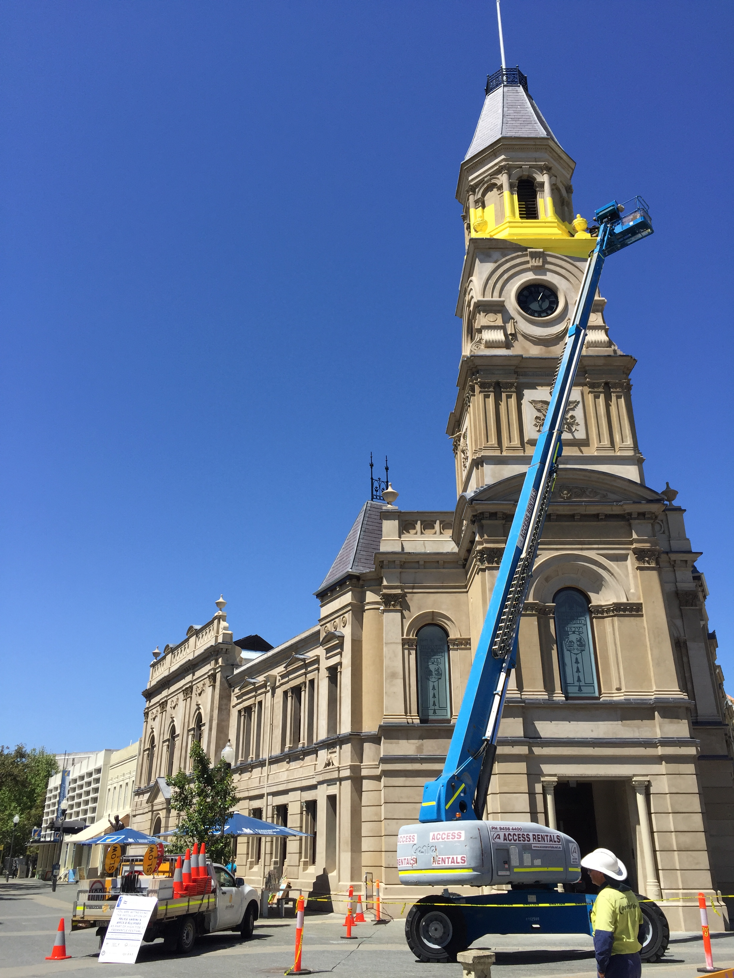 Progress shot of the High Tide artwork installation. Yellow paint is being applied to the Fremantle Town Hall via a blue crane.