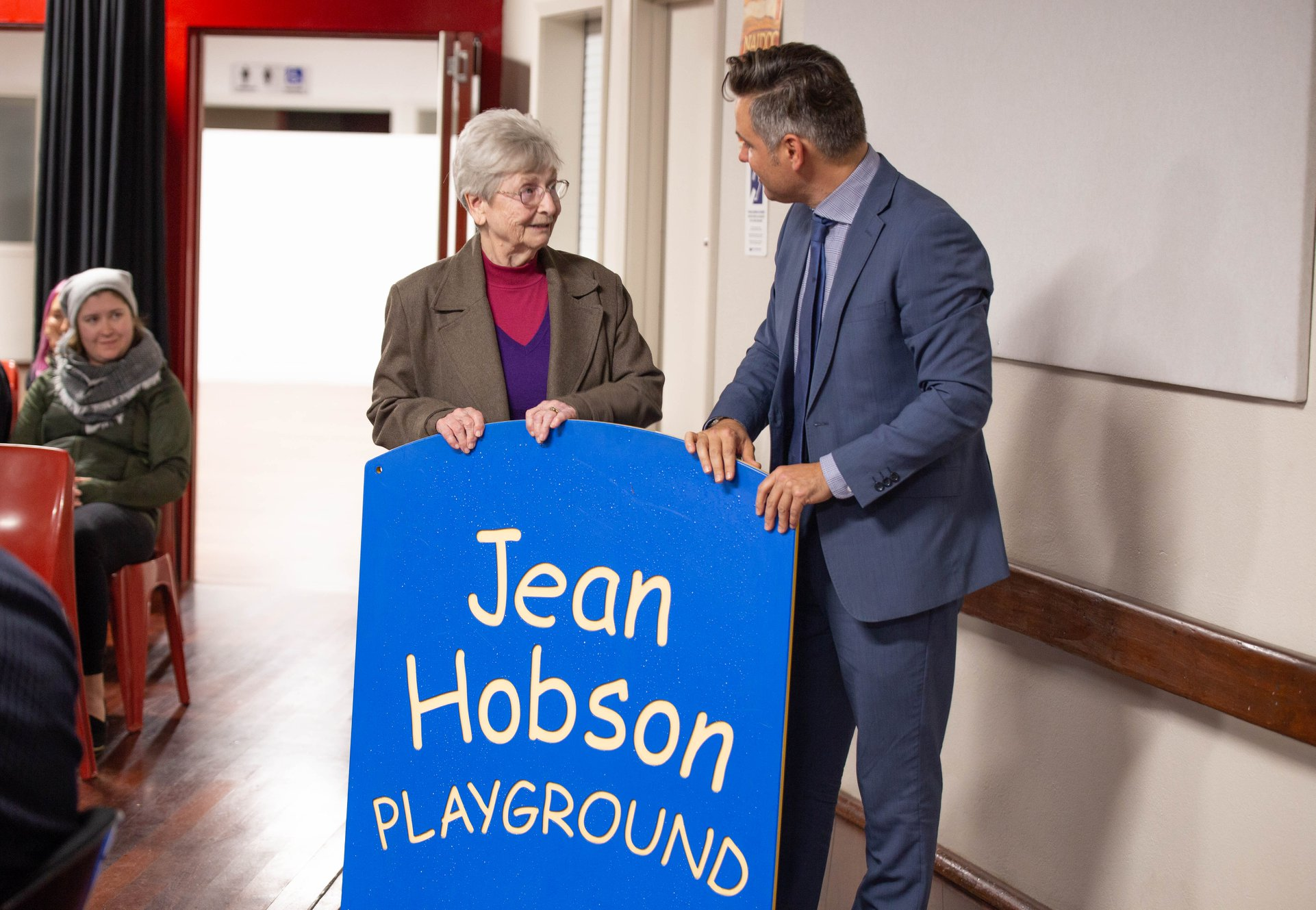 Jean Hobson and Mayor Pettitt standing behind the Jean Hobson playground sign