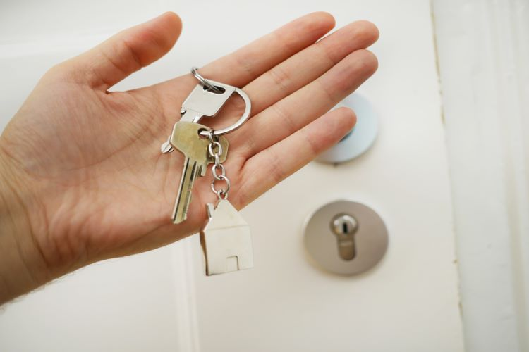 Set of keys held in hand with door to house in background