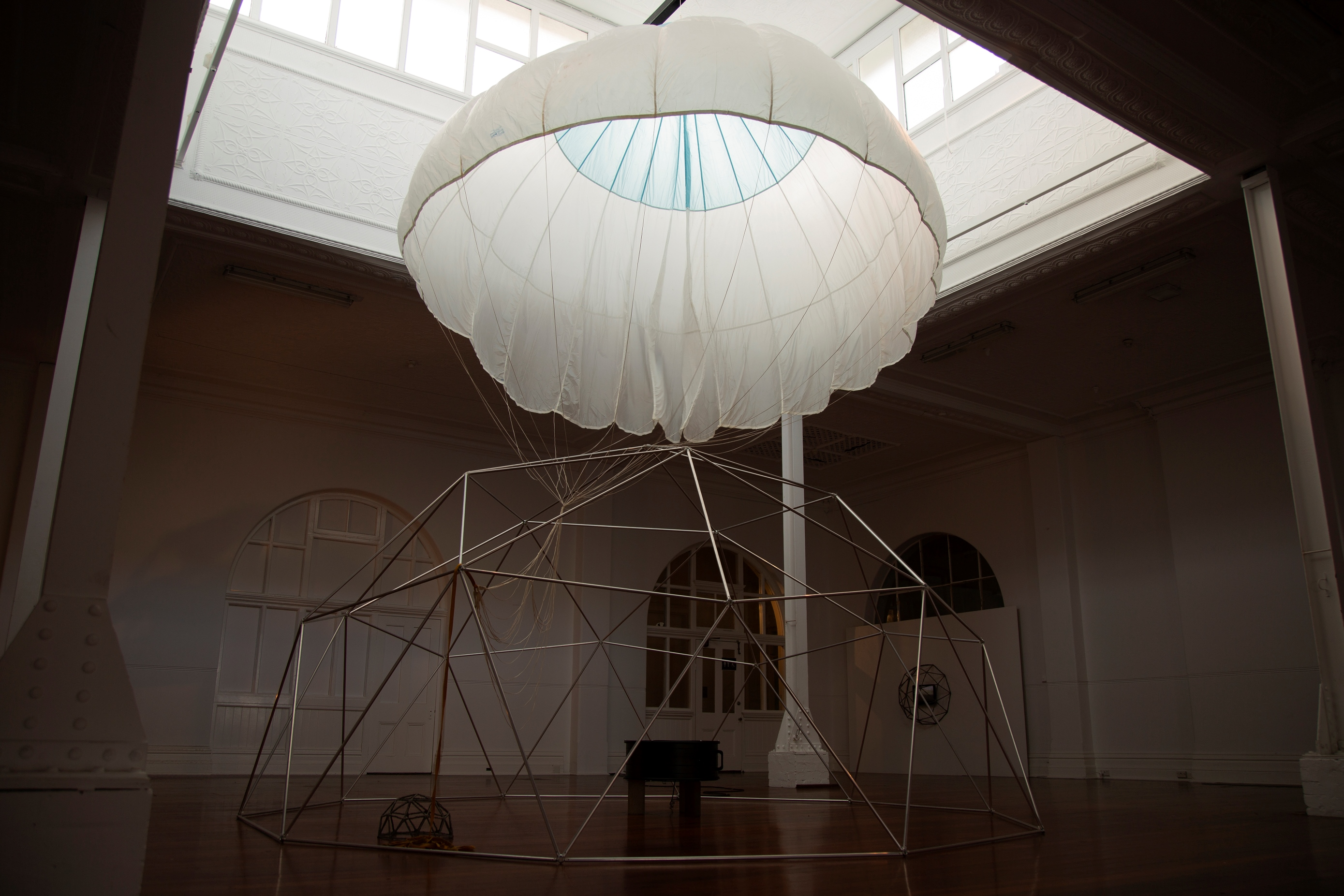 A photograph of an art installation created by Amy Perejuan-Capone. A white parachute is inflated and hovering over an dome metal structure which encloses another metal dome within is boundaries.