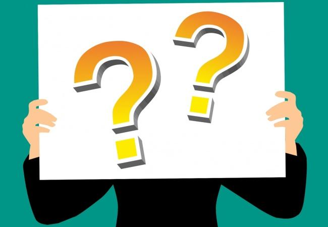 Clipart of a person holding up a sign with question marks on the front.
